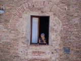 Old lady in a window in San Gimignano